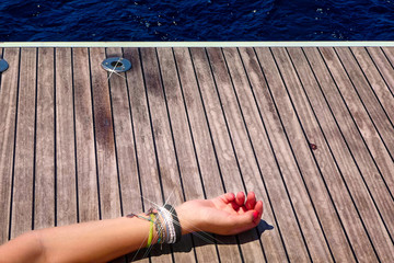 Female arm with jewelery at the deck of a yacht in Greece