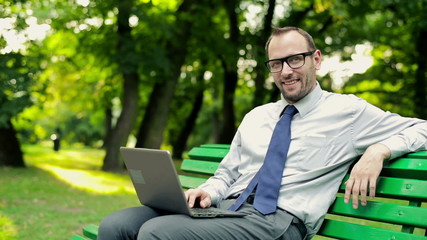 Happy businessman with laptop in the park