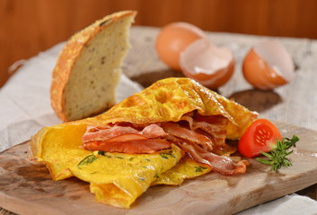 Breakfast omelette with ham, bacon and vegetables close up