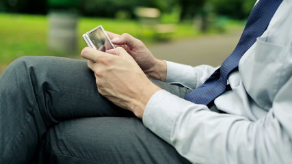 Businessman hands with smartphone in the park