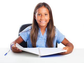 Girl smiling while doing her homeworks on a white background