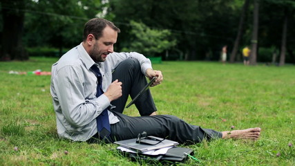 Businessman with tablet computer in the park