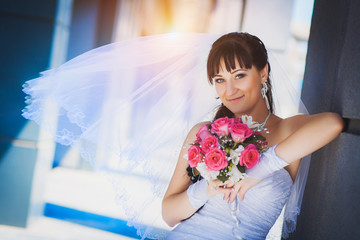 bride against a blue modern building background
