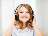 Fototapety little girl with headphones at home