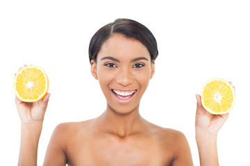 Cheerful attractive model holding slices of orange in both hands