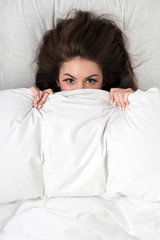 Portrait of a young woman lying in bed hiding under duvet.