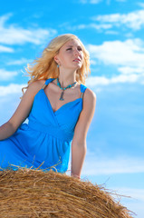 Beautiful young womanin blue dress  is sitting on stack