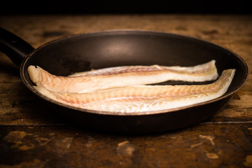 Two haddock fillets in frying pan