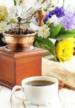 Drewniany młynek do kawy i filiżanka na stole