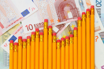 Graph of pencils against background of euro banknotes