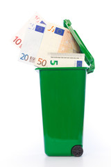Euro banknotes in green wheelie bin