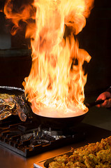 Professional cook preparing food on flame