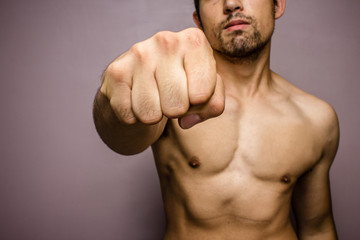 Young man with muscular physique punching