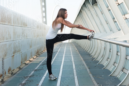 Young woman stretching her legs outdoors in modern enviroment.