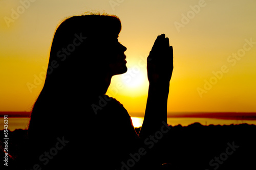 silhouette of a girl raises her hands to God