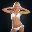 Beautiful blonde woman portrait with white bikini on black