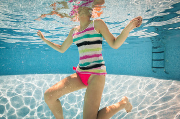 Girl portrait underwater with colorful singlet in swimming pool.