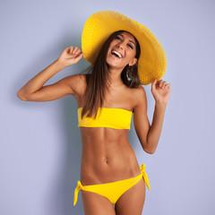 Beautiful smiling bikini girl against colorful purple background