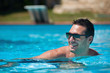 Handsome and happy man portrait in swimming pool.