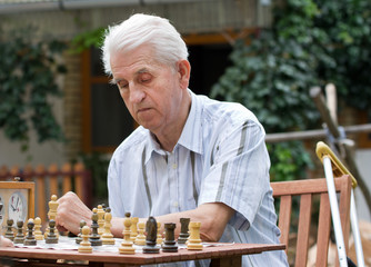 Pensioner playing chess in courtyard