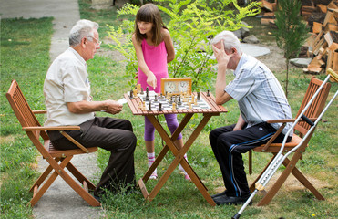 Young girl shows her grandpa how to play chess