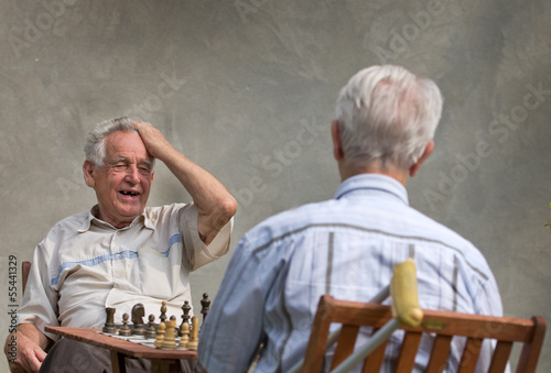 Pensioners playing chess in courtyard
