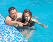 Father and daughter swimming in the poo