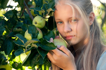 Outdoor portrait of beautiful blonde girl posing near apple tree