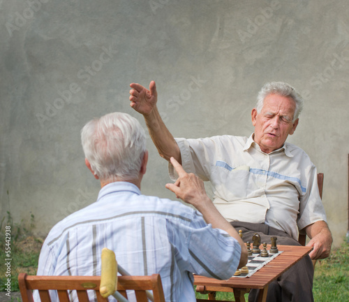 Pensioners talking and playing chess