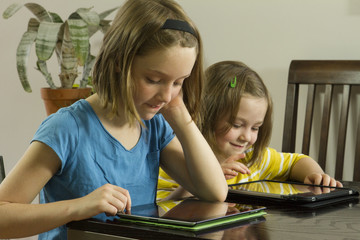 Young girls working on e-tablets, horizontal