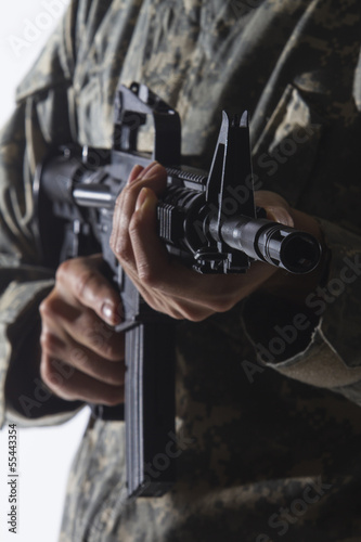 Military personnel holding gun, vertical