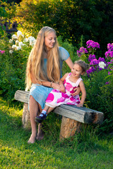 Beautiful blond young girl with her little sister in the country