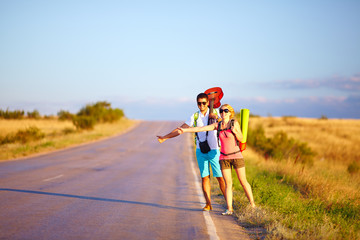 young people traveling hitchhiking. summer road