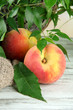 Ripe sweet peaches on wooden table, close up