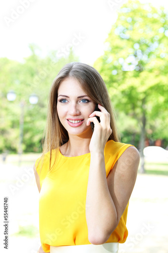 Beautiful young woman  speaking on mobile phone at summer park