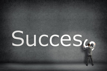 Businessman collects on the wall the word success
