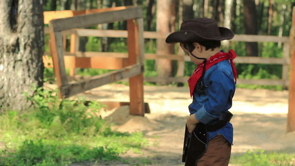 Little Cowboy is playing with a toy gun