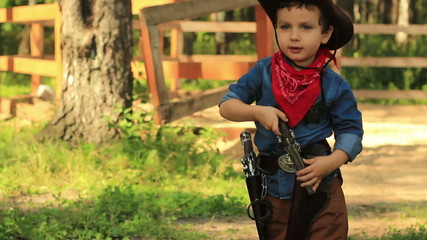Little Cowboy puts the gun in his holster