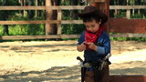 Little Cowboy standing near a wooden fence paddocks
