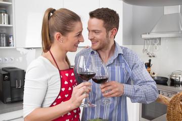 Verliebtes junges Paar in der Küche beim Wein trinken