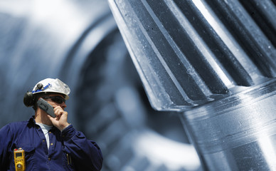 industry worker with large machinery gears