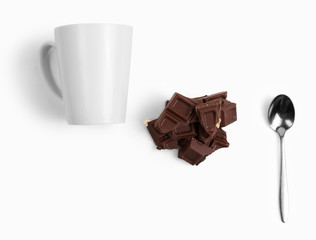 Small spoon, white mug, chocolate pieces. On white background