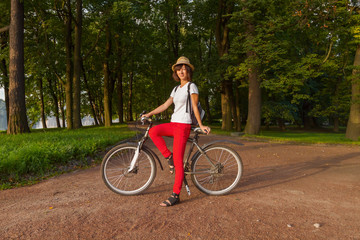 Hipster beautiful girl on a bicycle in the park