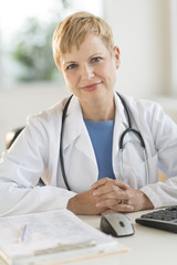 Confident Female Doctor Sitting At Desk