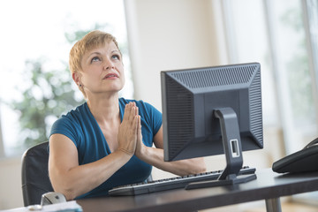 Businesswoman Praying While Sitting At Desk