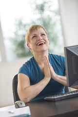 Happy Businesswoman Praying At Desk In Office