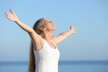 Attractive blonde woman breathing happy with raised arms