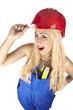 Lustige Handwekerin mit Blaumann und rotem Bauhelm