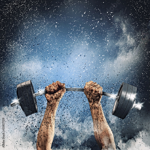 Human hands lifting barbell