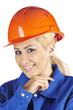 Fröhliche Handwerkerin mit Blaumann und rotem Bauhelm
